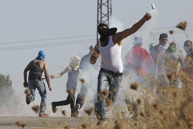 Un Palestinien relance une bombe lacrymogène tirée par... (PHOTO JAAFAR ASHTIYEH, AFP)