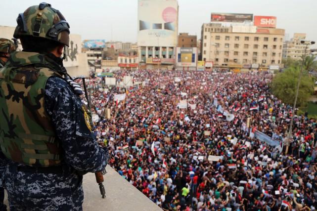 Un policier surveille la foule de manifestants réunis... (Photo Karim Kadim, archives AP)