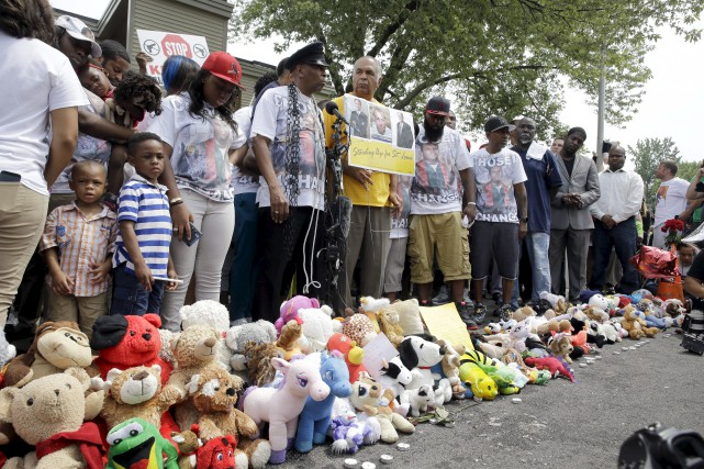 Des proches de Michael Brown observent une minute... (Associated Press)