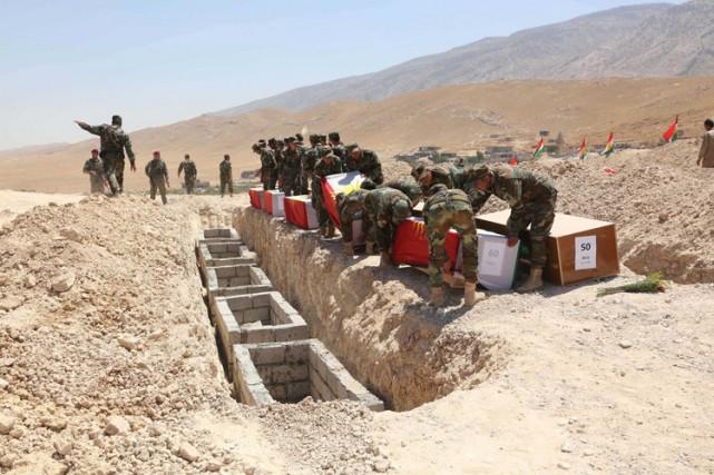 Des membres des forces kurdesportent des cercueils contenant... (PHOTO REUTERS)