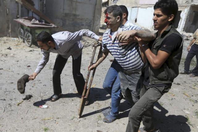 Des hommes aident un blessé à la suite... (PHOTO BASSAM KHABIEH, REUTERS)