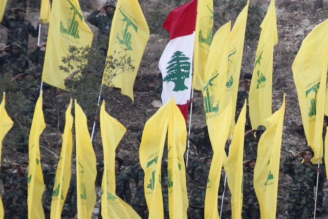 Des drapeaux du Hezbollah entourent un drapeau libanais.... (PHOTO ARCHIVES REUTERS)