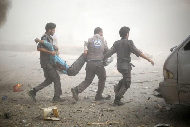 Des secouristes transportent un homme blessé lors defrappes... (PHOTO SAMEER AL-DOUMY, AFP)