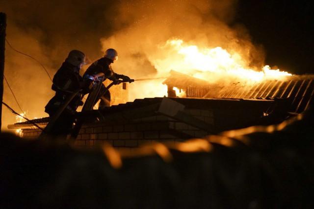 Des pompiers tentent d'éteindre un incendie détruisant une... (PHOTO MSTYSLAV CHERNOV, ARCHIVES AP)