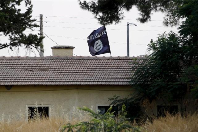 Un drapeau de l'État islamique flotte au-dessus d'une... (Photo archives AP)