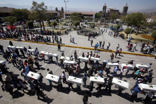 Des gens portent les cercueuils jusqu'au lieu des... (PHOTO MAX CABELLO, ARCHIVES AFP)