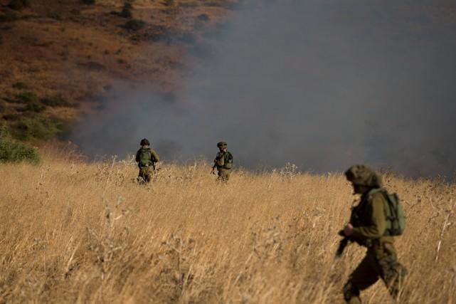 Des soldats israéliens patrouillent près d'une zone enfumée... (Photo Reuters)