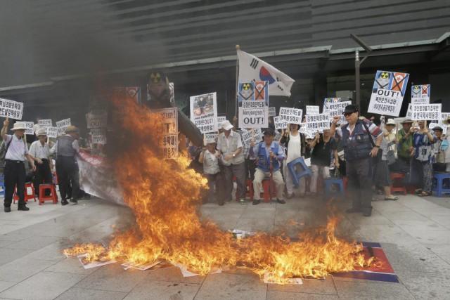 Des manifestants sud-coréens ont brûlé des affiches à... (PHOTO AHN YOUNG-JOON, AP)