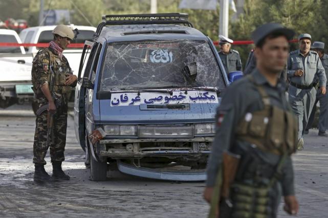 Des militaires inspectent un véhicule endommagé par la... (PHOTO MOHAMMAD ISMAIL, REUTERS)