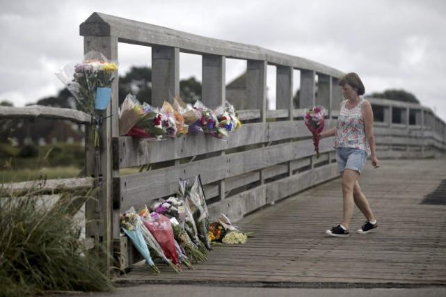 Une femme dépose des fleurs sur un pont... (PHOTO DANIEL LEAL-OLIVAS, AP)