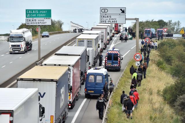 Des policiers empêchent des migrants de se rendre... (Photo archives AFP)