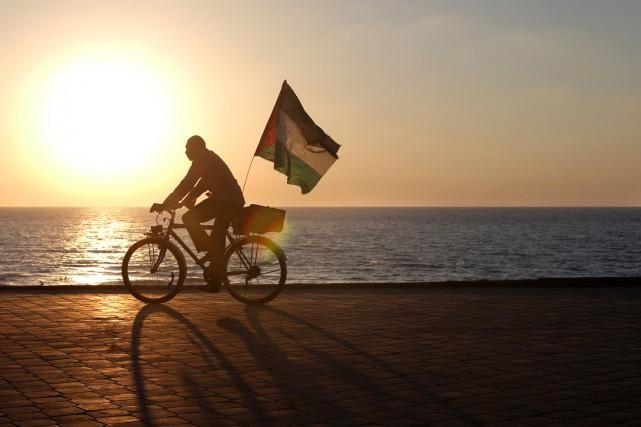 Un homme se promène à vélo, un drapeau... (PHOTO MOHAMMED ABED, ARCHIVES AFP)