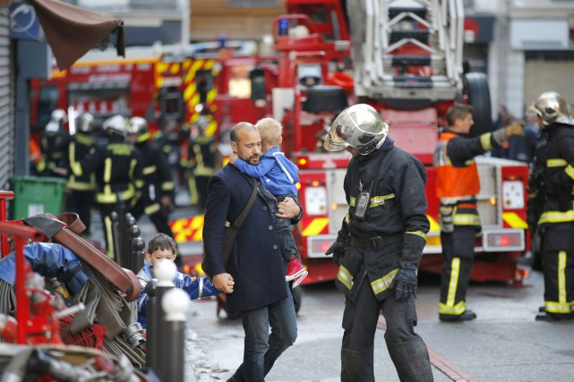 Un pompier évacue une famille après qu'un incendie... (PHOTO FRANÇOIS MORI, AP)