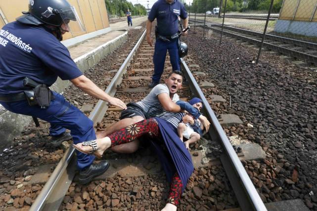 Des policiers hongrois entourent une famille de migrants... (PHOTO LASZLO BALOGH, REUTERS)