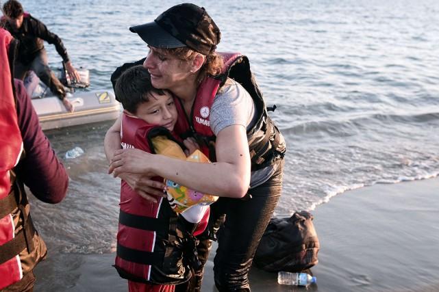 Une femme serre son fils dans ses bras... (Photo LOUISA GOULIAMAKIO, AFP)