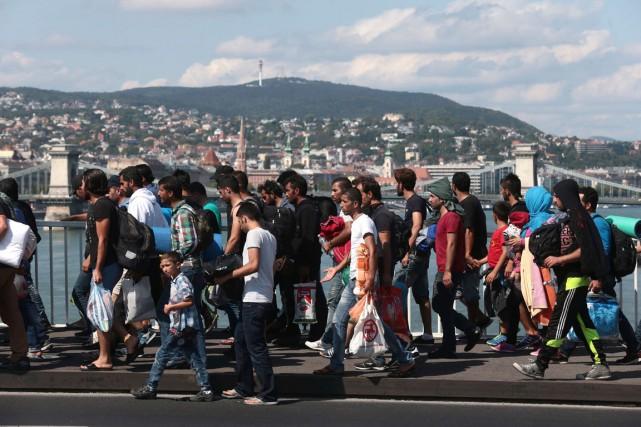 Des réfugiés marchent par centaines sur le pont... (Photo AFP, FERENC ISZA)