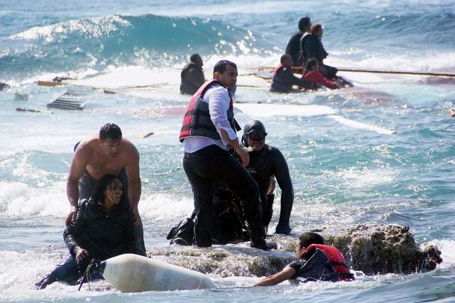 Un sauveteur aide une femme qui était à... (Photo Argiris Mantikos/Eurokinissi, AP)