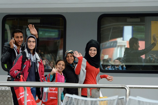 Des migrants qui arrivent à Munich saluent les... (PHOTO CHRISTOF STACHE, AFP)