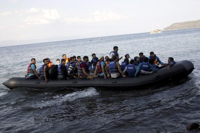 Des réfugiés syriens se dirigent vers le rivage... (AFP, ANGELOS TZORTZINIS)