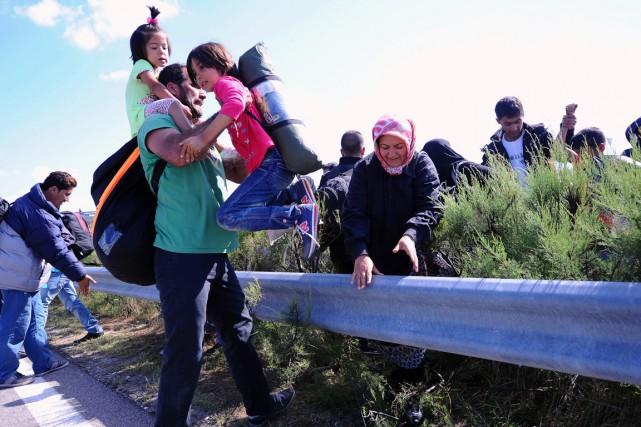 Des migrants traversent une glissière de sécurité en... (PHOTO ATTILA KISBENEDEK, AFP)