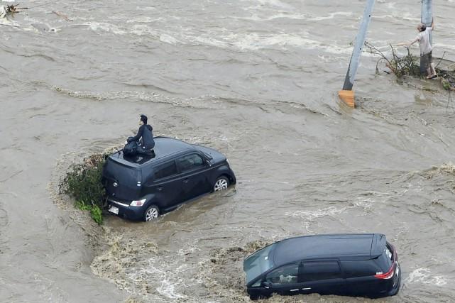 Deux personnes attendent désespérément les secours: une sur... (PHOTO REUTERS/KYODO)