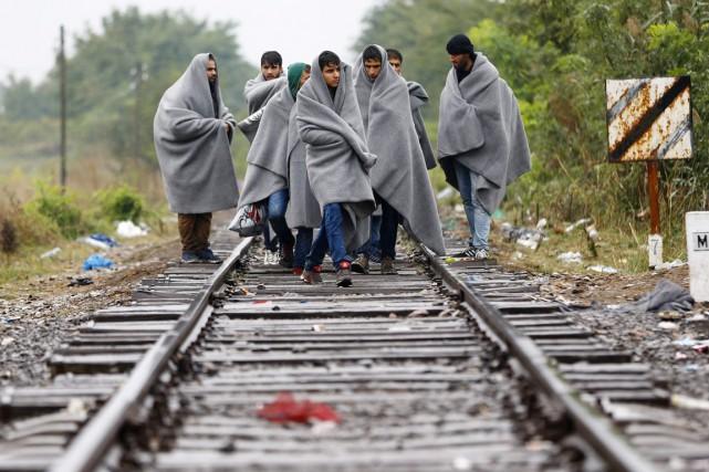 Des migrants, recouverts d'une couverture, traversent la frontière... (PHOTO MATTHIAS SCHRADER, AP)