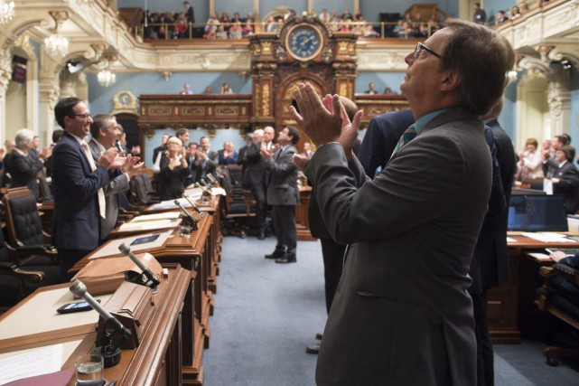 Les députés de l'Assemblée nationale applaudissent alors qu'on...