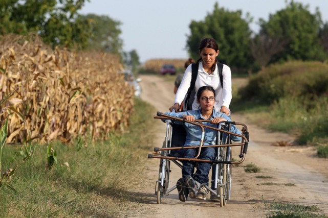 Une migrante en chaise roulante se dirige vers... (PHOTO AFP)