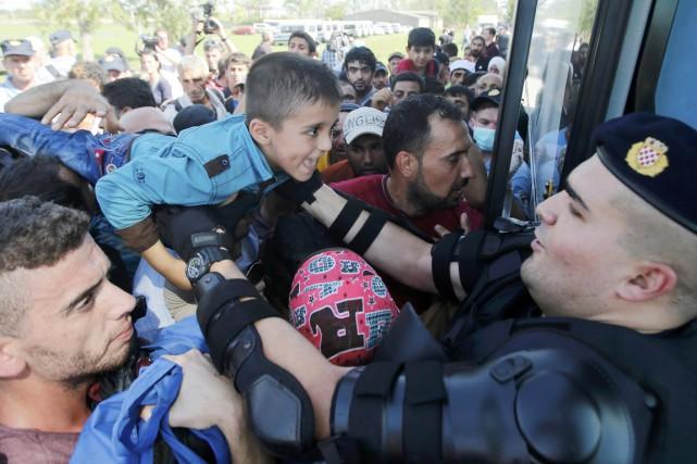 Un policier croate aide un jeune garçon à... (PHOTO ANTONIO BRONIC, REUTERS)
