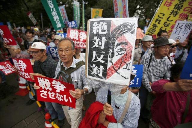 Des militants pacifistes manifestent devant le Parlement, brandissant... (PHOTO KOJI UEDA, AP)