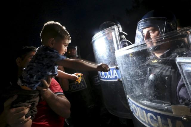 Un homme montre son enfant à un policier... (Photo Srdjan Zivulovic, Reuters)