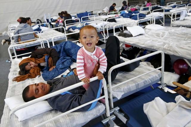 Une famille se repose dans un gymnase transformé... (Photo Kai Pfaffenbach, Reuters)