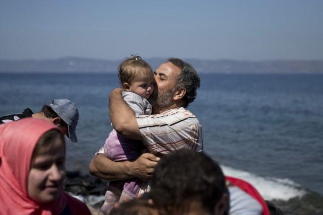 Un père embrasse sa fillette après leur arrivée... (Photo Petros Giannakouris, AP)