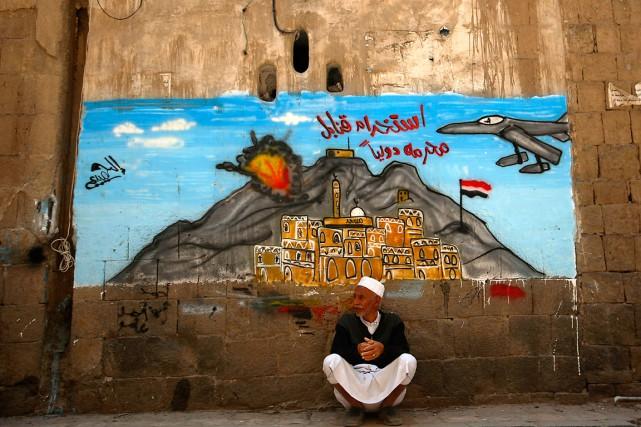 Un homme se repose devant un graffiti qui... (Photo Hani Mohammed, AP)