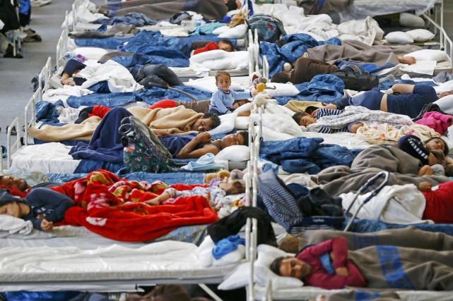 Des migrants et des réfugiés se reposent dans... (PHOTO KAI PFAFFENBACH, REUTERS)