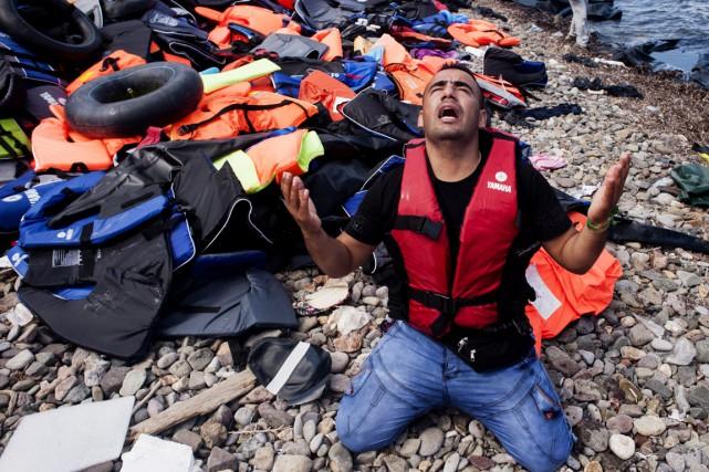 Un homme turc prie à son arrivée sur... (PHOTO IAKOVOS HATZISTAVROU, AFP)