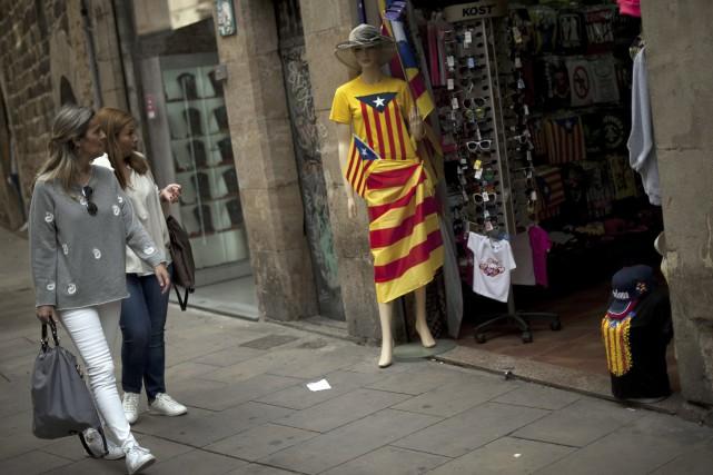 Deux femmes marchent près d'une boutique à Barcelone... (Agence France-Presse)