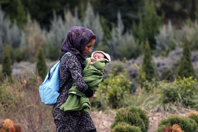 Une migrante transporte son enfant et son maigre... (Photo Petr David Josek, AP)