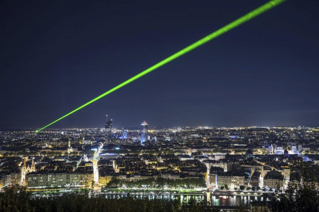 Un rayon de laser vert perce le ciel... (PHOTO JEFF PACHOUD, AGENCE FRANCE-PRESSE)