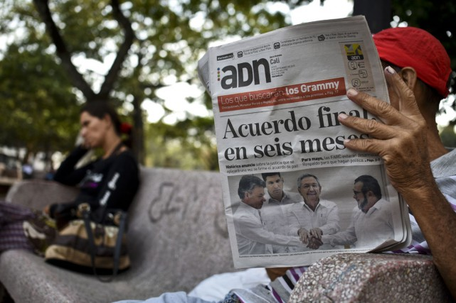 Un Colombien lit le journal du 24 septembre... (Photo LUIS ROBAYO, archives AFP)