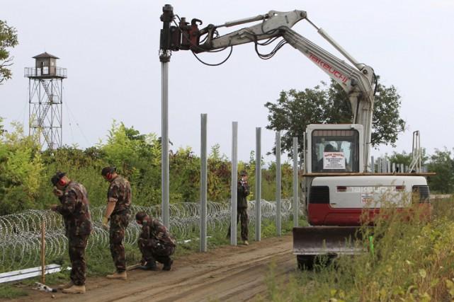 Des soldats hongrois érigent une clôture à la... (PHOTO REUTERS)