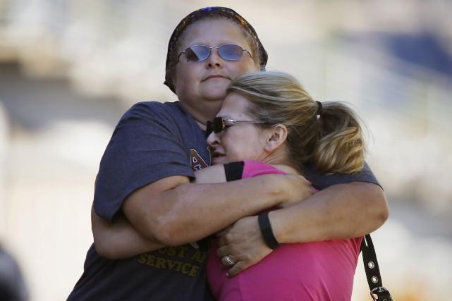 Des femmes se réconfortent alors qu'elles s'apprêtent à... (AP, John Locher)