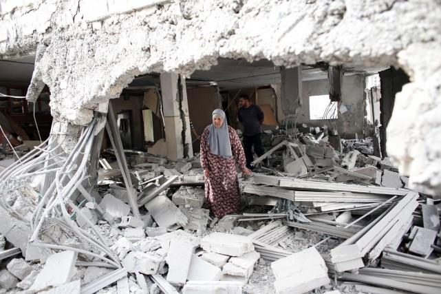 Une Palestinienne marche dans les ruines d'une maison... (PHOTO THOMAS COEX, AFP)