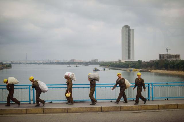 Des ouvriers chargés de sacs traversent un pont... (PHOTO ED JONES, AFP)