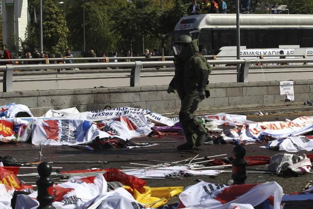 Un expert en desarmoçage de bombes marchent près... (Agence France-Presse)
