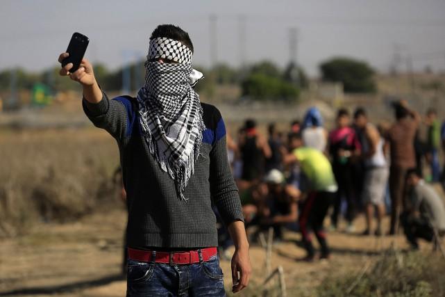 Un Palestinien masqué prend des photos de soldats... (PHOTO MOHAMMED ABED, AFP)
