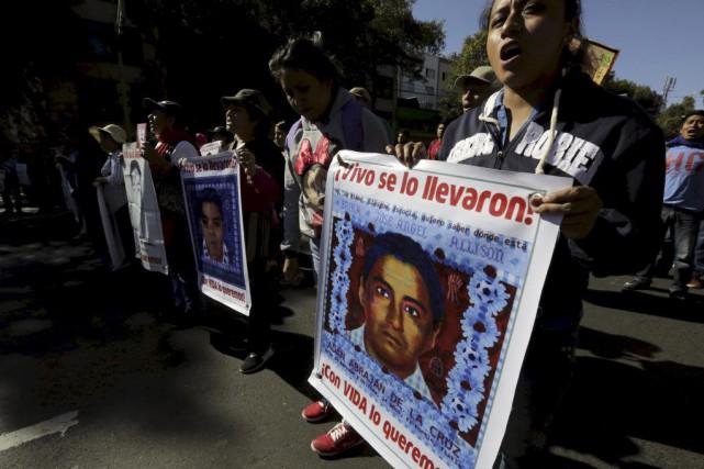 Des proches des étudiants disparus tiennent des affiches... (HENRY ROMERO)