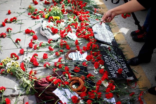 Des gens se recueillent durant un hommage aux... (AP, Emrah Gurel)