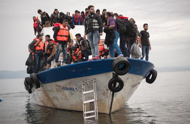 Des migrants et des réfugiés débarquent d'un bateau... (PHOTO FOTIS PLEGAS G, ARCHIVES REUTERS)