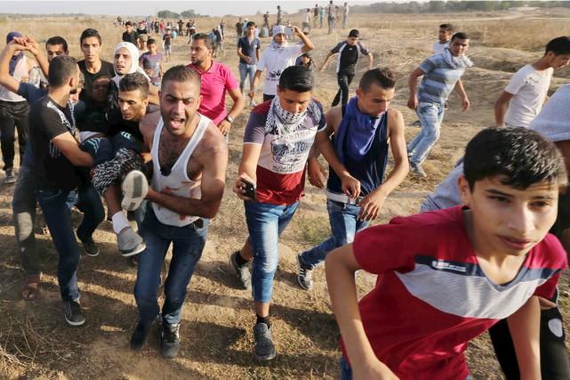 Un protestataire palestinien blessé par balle par un... (PHOTO IBRAHEEM ABU MUSTAFA, REUTERS)